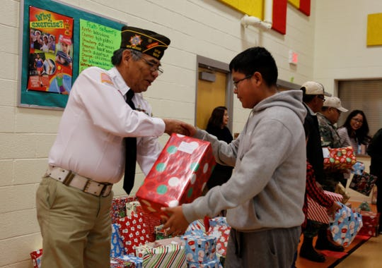 Shiprock Chapter Veterans Organization member Tommy Yazzie, left, helps distribute Christmas gifts on Saturday at the Shiprock Youth Complex.