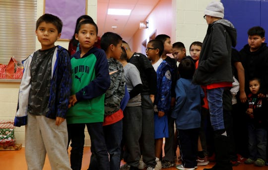 Boys line up on Saturday to receive gifts donated to Operation Blessing by veterans and community groups.