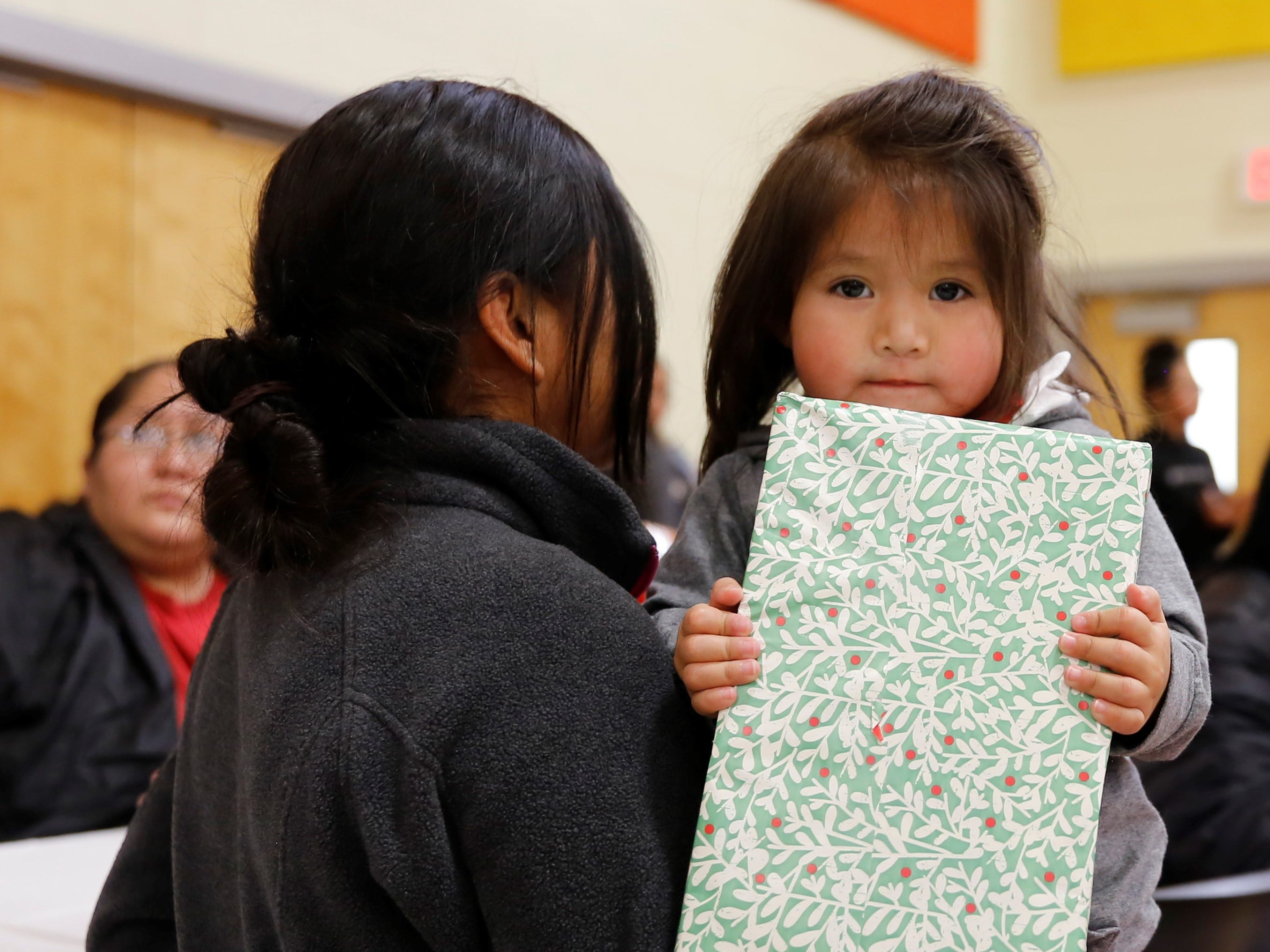 Mae Benally waits to open her gift during the Operation Blessing event on Saturday at the Shiprock Youth Complex.
