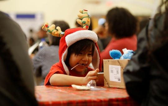 Chase Duncan, 4, watches a video while waiting for the gift distribution to start on Saturday at the Shiprock Youth Complex.