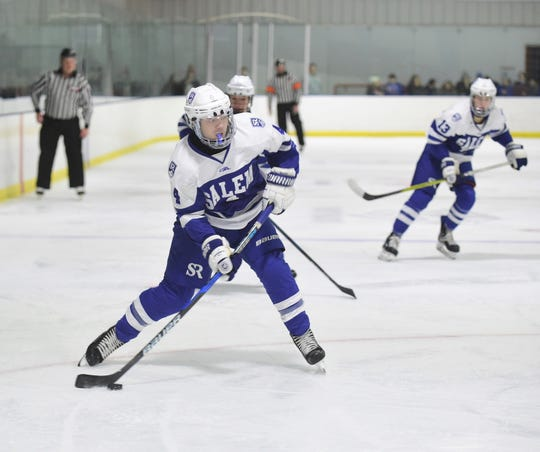 Salem's Garrett Christie (4) looks to send the puck toward the Canton net, with teammate Anthony Gattoni (13) trailing on the play.