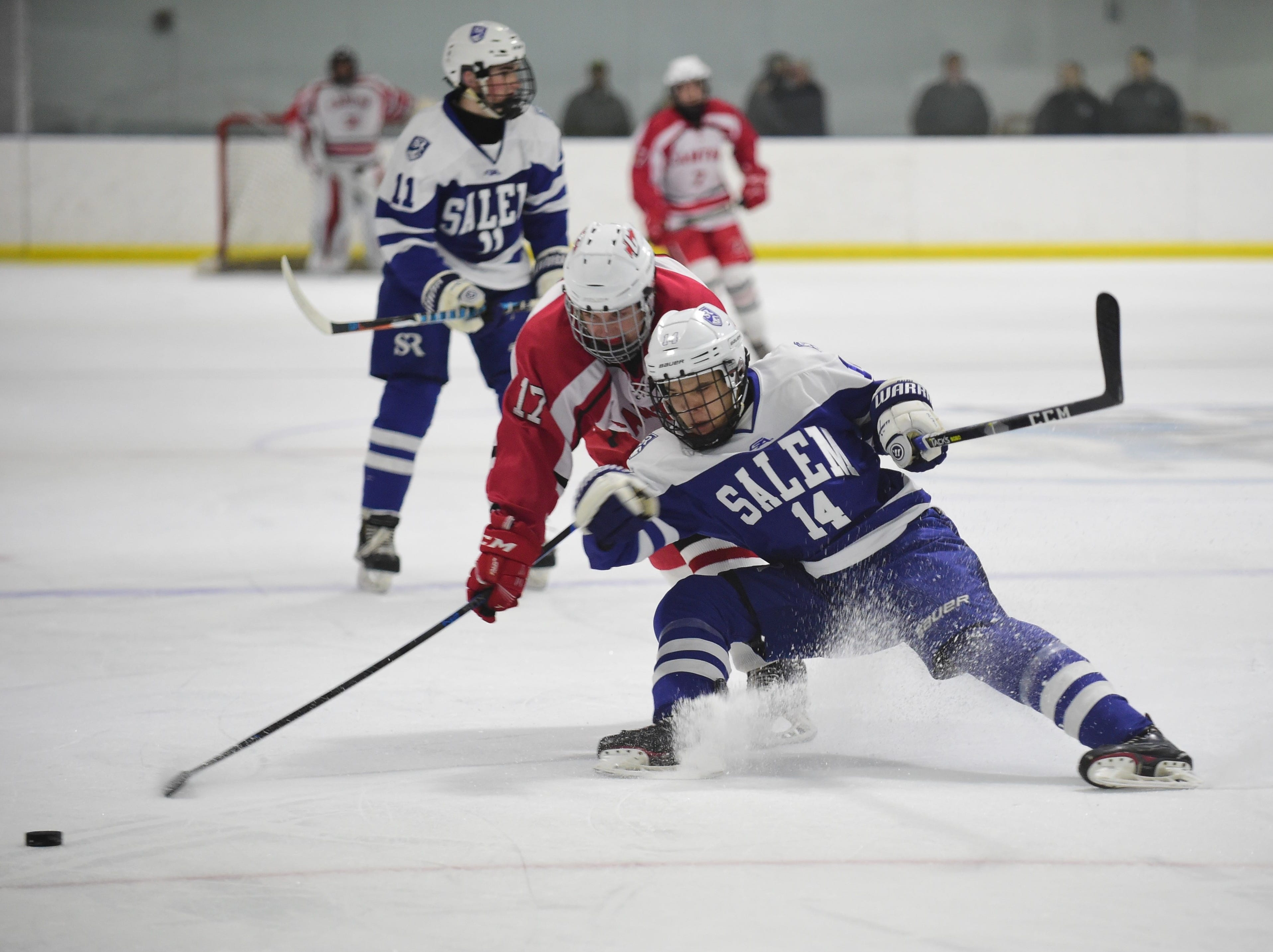 Salem's Nick Brosky (14) battles with Canton's Declan O'Hare (17) for a puck in the neutral zone.