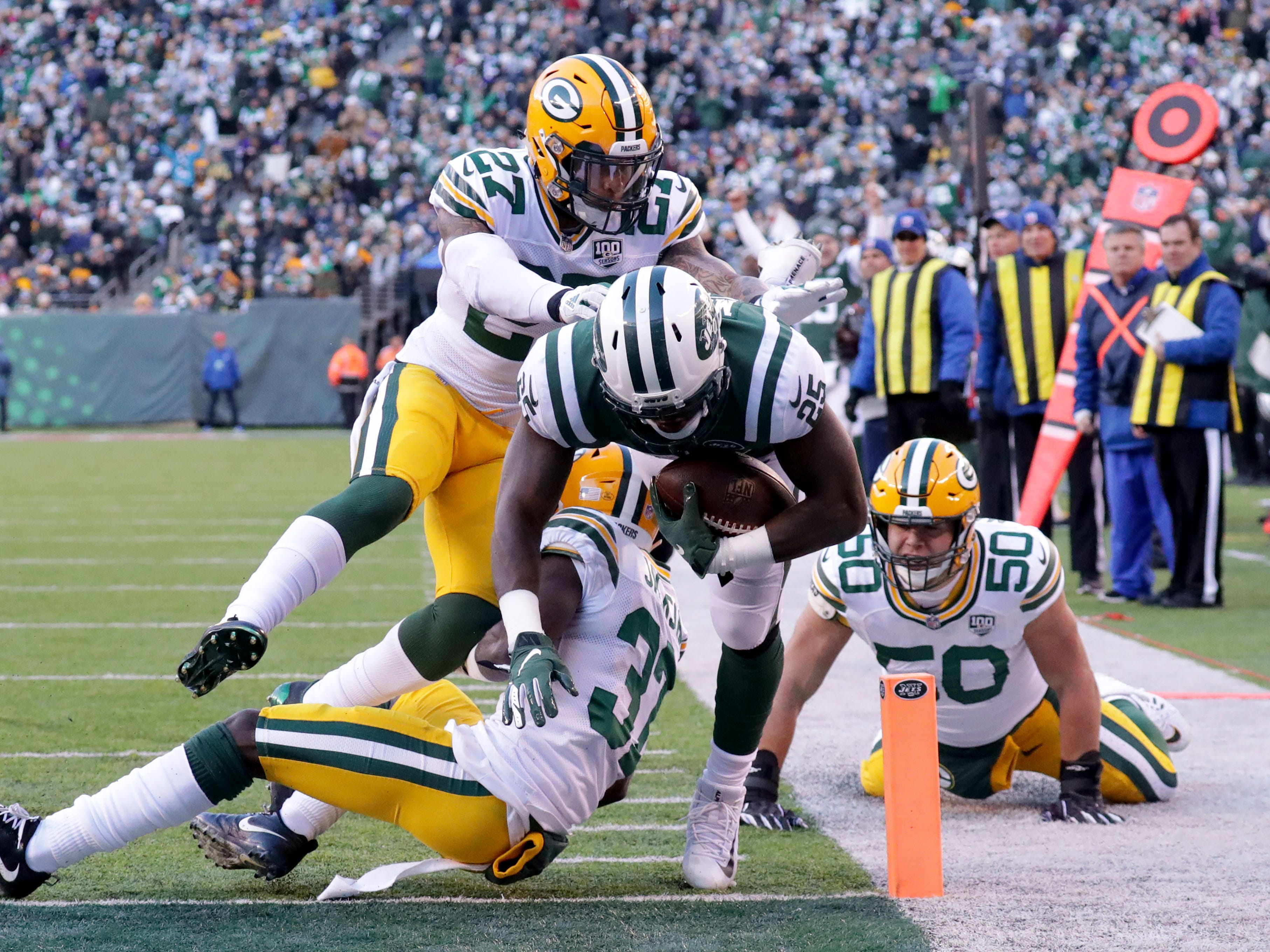 New York Jets' Elijah McGuire scores a touchdown  against Green Bay Packers' Josh Jones (27), Josh Jackson (37) and Blake Martinez (50) during the 2nd half of Packers 44-38 overtime win against the New York Jets at MetLife Stadium Sunday, Dec. 23, 2018, in East Rutherford.