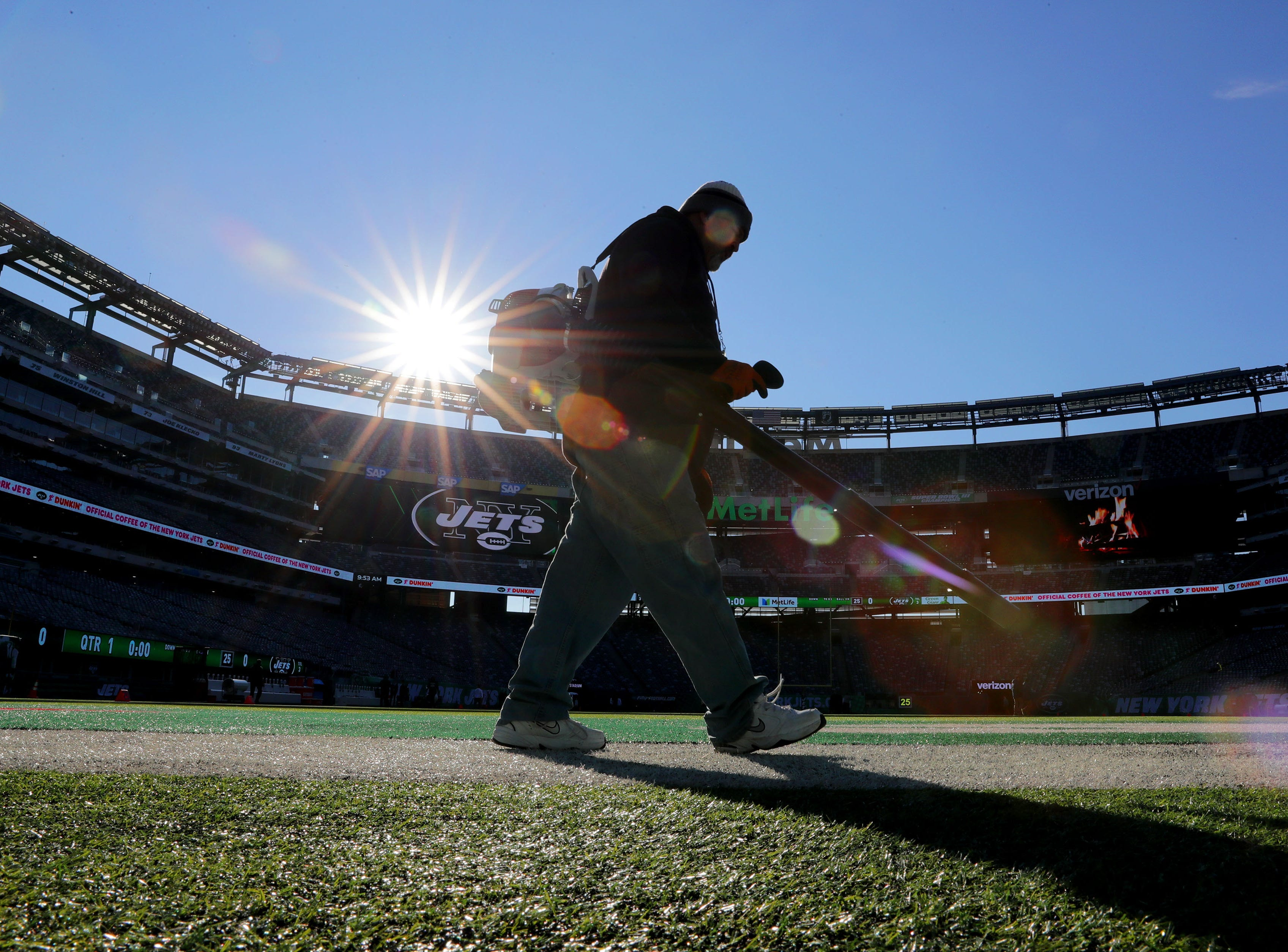A member of the New York Jets  grounds crew blows off the artificial turf before the Green Bay Packers game against the New York Jets at MetLife Stadium Sunday, Dec. 23, 2018, in East Rutherford.