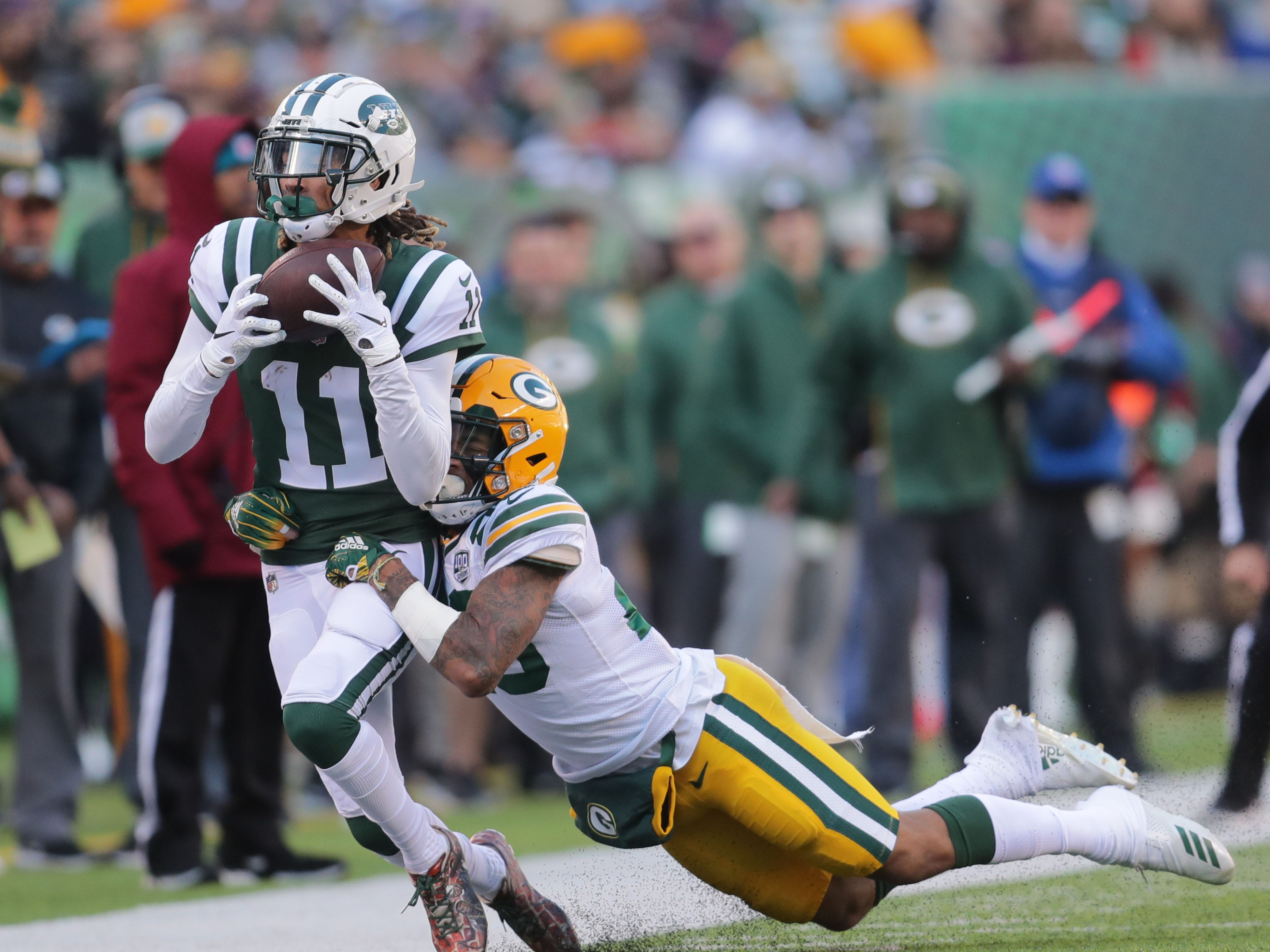 New York Jets' Robby Anderson (11) makes a sidelines catch tacked by Green Bay Packers' Jaire Alexander during first half of the Green Bay Packers game against the New York Jets at MetLife Stadium Sunday, Dec. 23, 2018, in East Rutherford.