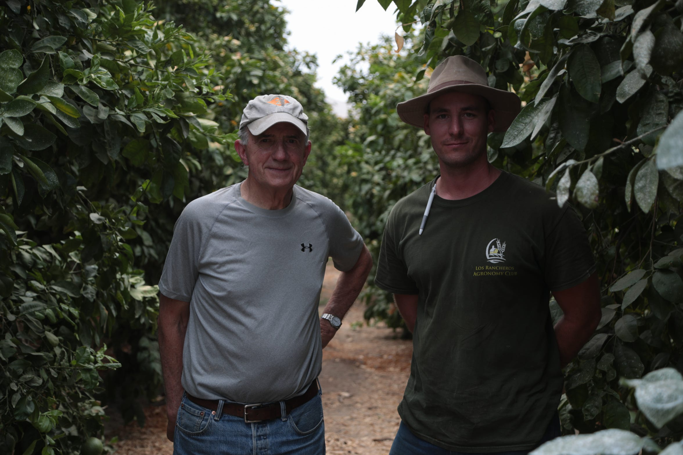 Jim Seley, left, and farm manager Zane Smiley stand between rows of citrus trees at Seley Ranches in Borrego Springs, Calif.
