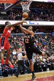Phoenix Suns forward T.J. Warren (12) goes to the basket against Washington Wizards guard Bradley Beal, left, during the first half of an NBA basketball game, Saturday, Dec. 22, 2018, in Washington. (AP Photo/Nick Wass)