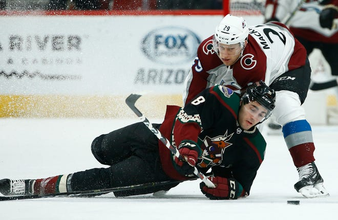 Arizona Coyotes center Nick Schmaltz (8) falls to the ice as he gets hit by Colorado Avalanche center Nathan MacKinnon (29) during the first period of an NHL hockey game Saturday, Dec. 22, 2018, in Glendale, Ariz. (AP Photo/Ross D. Franklin)