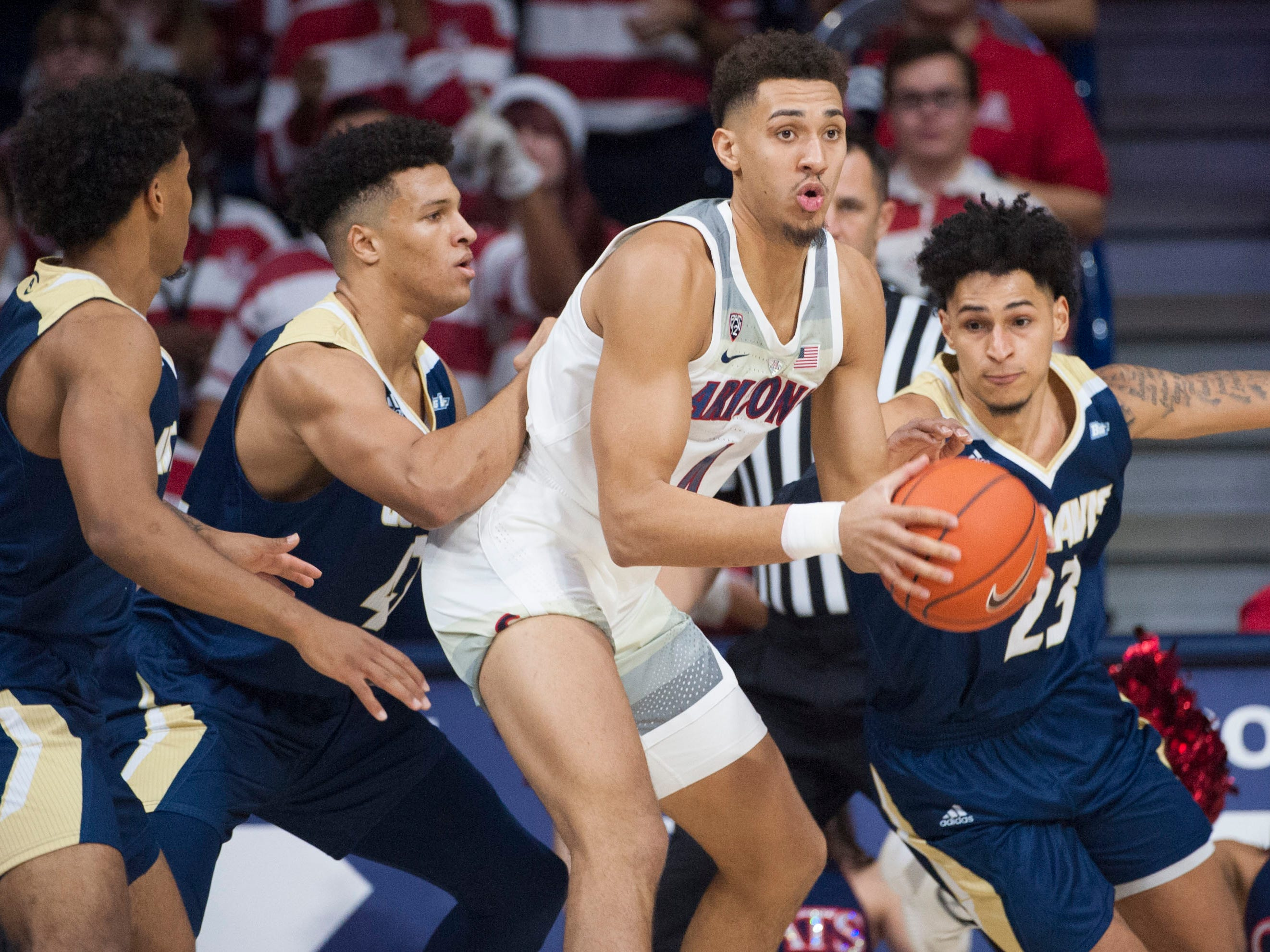 Dec 22, 2018; Tucson, AZ, USA; Arizona Wildcats center Chase Jeter (4) looks to pass the ball as UC Davis Aggies guard Rogers Printup (23) (right) guard Damion Squire (1) (left) and forward Jonah Underwood (42) defend during the first half at McKale Center. Mandatory Credit: Casey Sapio-USA TODAY Sports