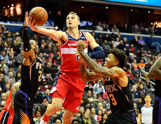 Dec 21, 2018; Washington, DC, USA; Washington Wizards forward Sam Dekker (8) shoots as Phoenix Suns forward Kelly Oubre Jr. (3) defends during the second quarter at Capital One Arena. Mandatory Credit: Brad Mills-USA TODAY Sports