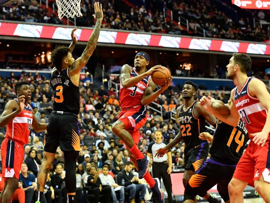 Dec 21, 2018; Washington, DC, USA; Washington Wizards guard Bradley Beal (3) shoots as Phoenix Suns forward Kelly Oubre Jr. (3) and center Deandre Ayton (22) defend during the second quarter at Capital One Arena. Mandatory Credit: Brad Mills-USA TODAY Sports