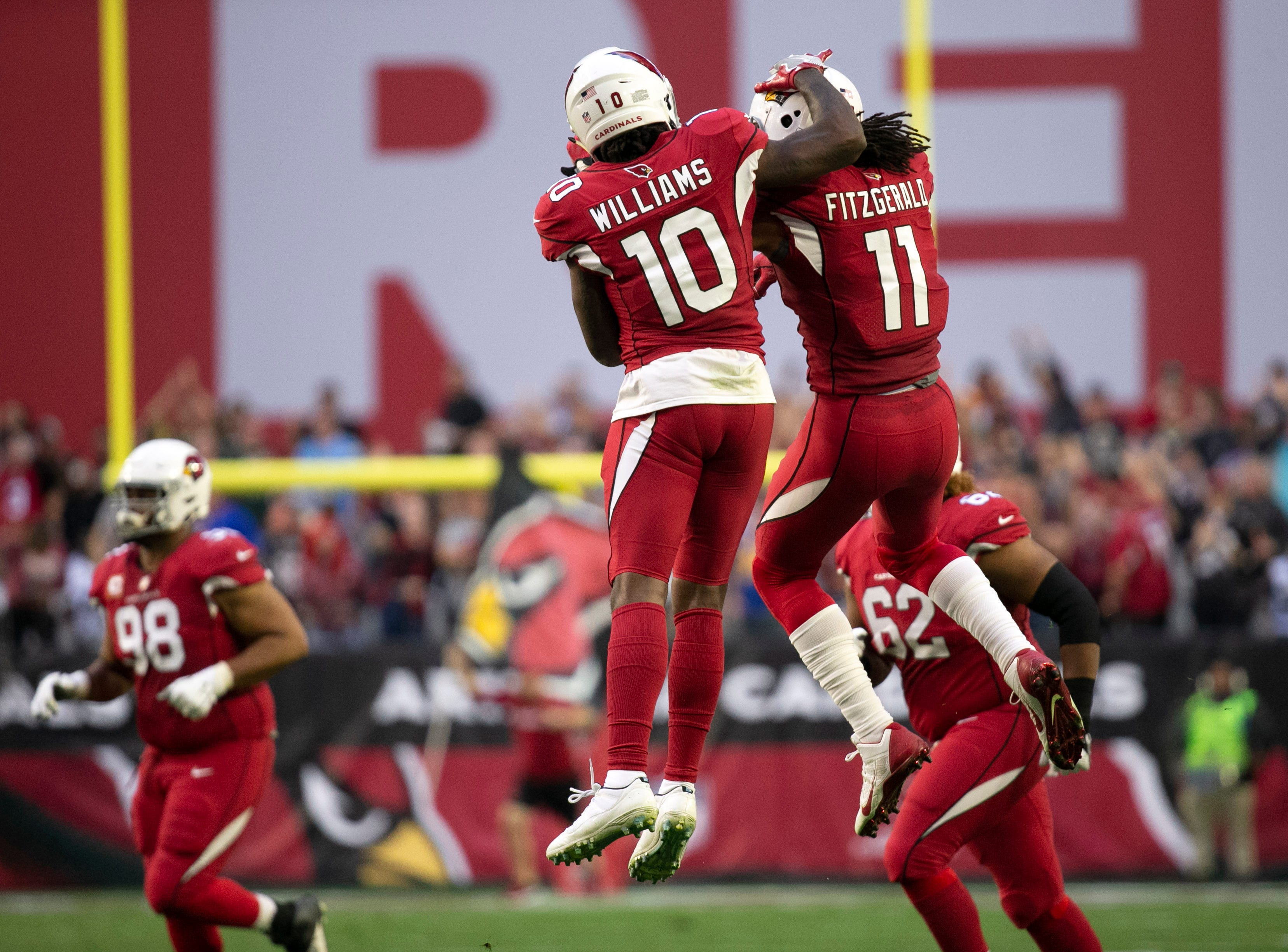 Cardinals wide receiver Larry Fitzgerald reacts with teammate Chad Williams after Fitzgerald threw a touchdown pass against the Rams during the second quarter of the NFL game at State Farm Stadium in Glendale on Sunday, December 23, 2018.