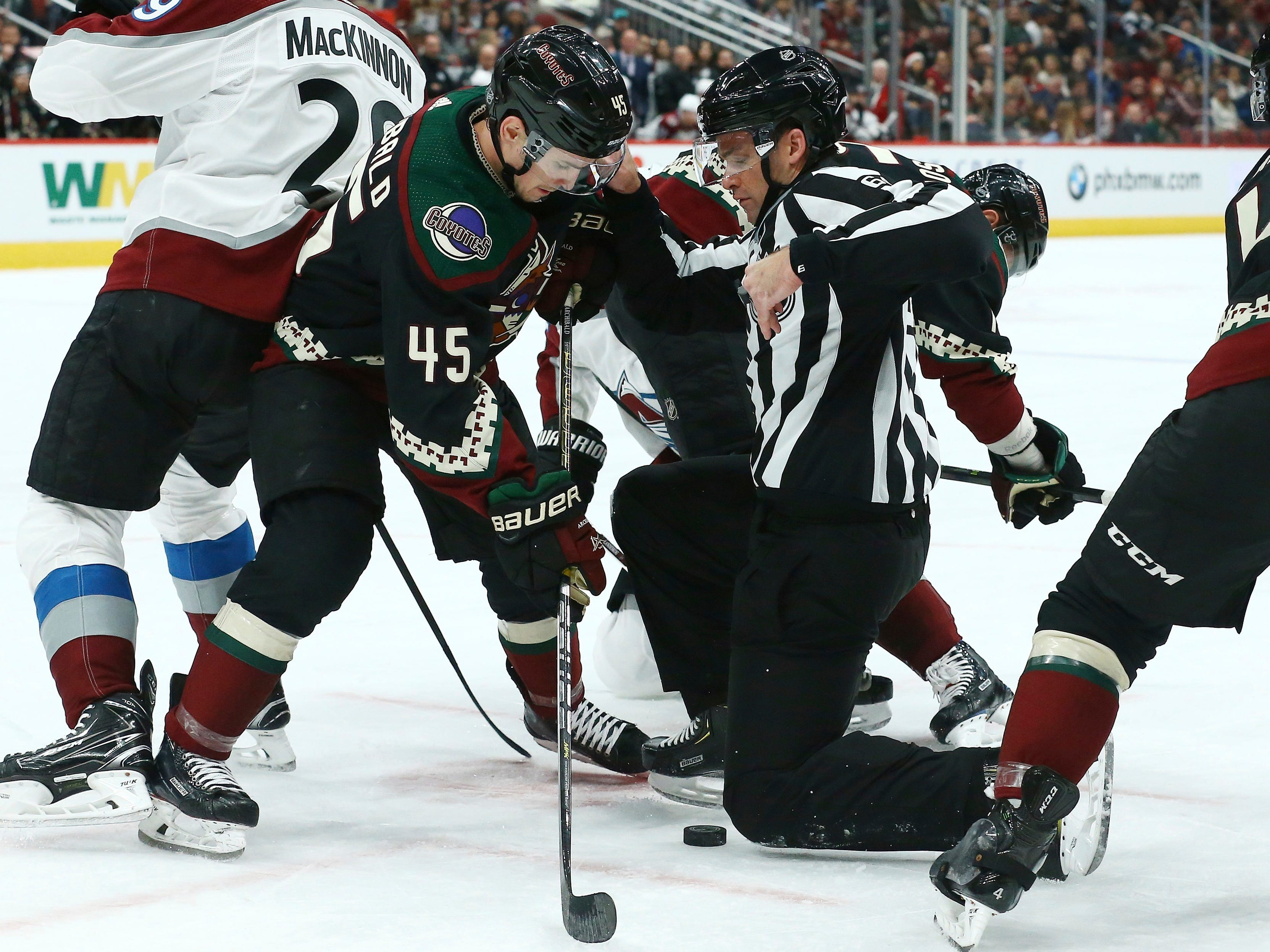 Arizona Coyotes right wing Josh Archibald (45) tries to get to the puck as linesman Brandon Gawryletz moves out of the way during the first period of an NHL hockey game against the Colorado Avalanche Saturday, Dec. 22, 2018, in Glendale, Ariz. (AP Photo/Ross D. Franklin)