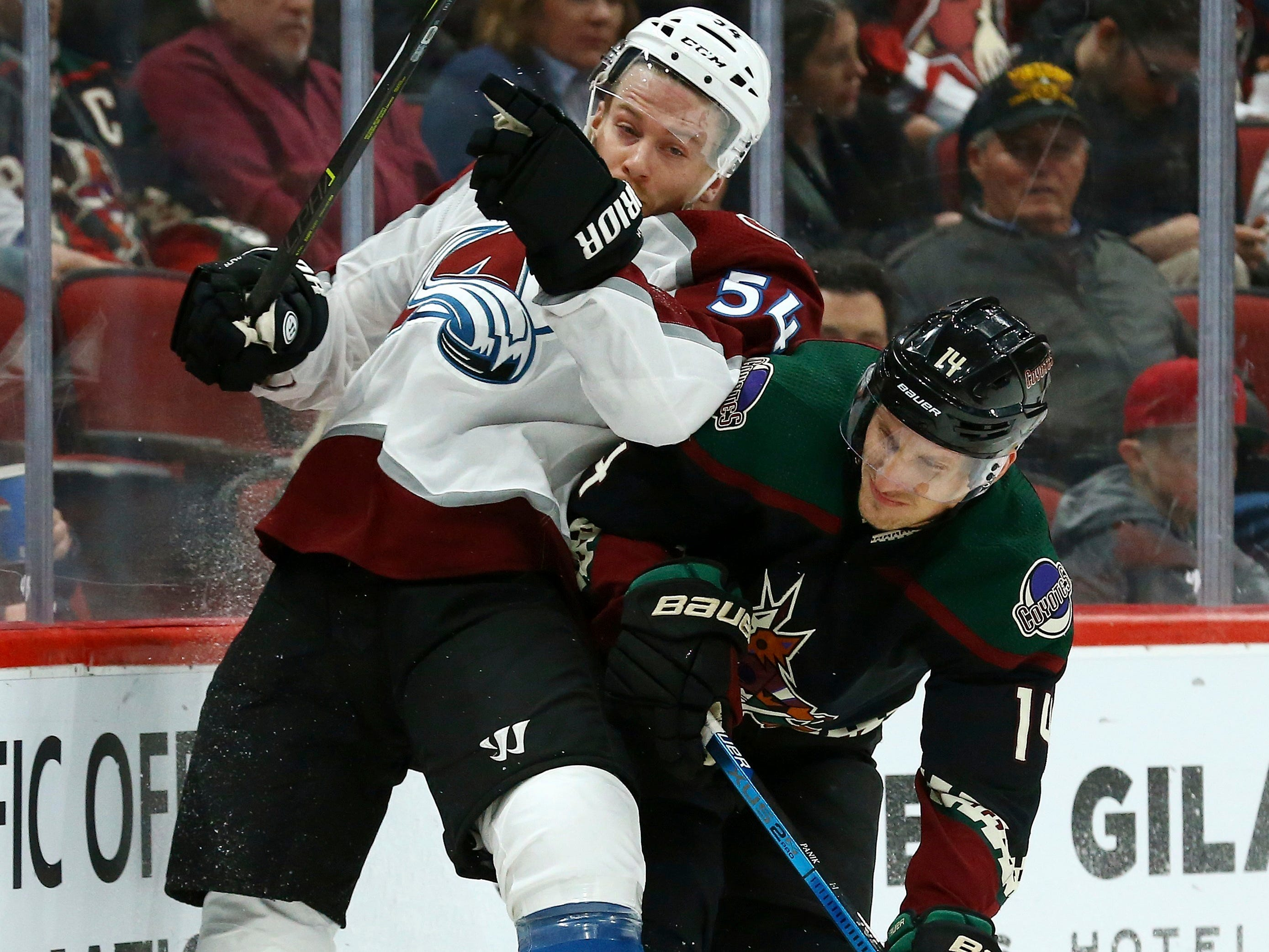 Arizona Coyotes right wing Richard Panik (14) checks Colorado Avalanche defenseman Anton Lindholm (54) into the boards during the second period of an NHL hockey game Saturday, Dec. 22, 2018, in Glendale, Ariz. (AP Photo/Ross D. Franklin)