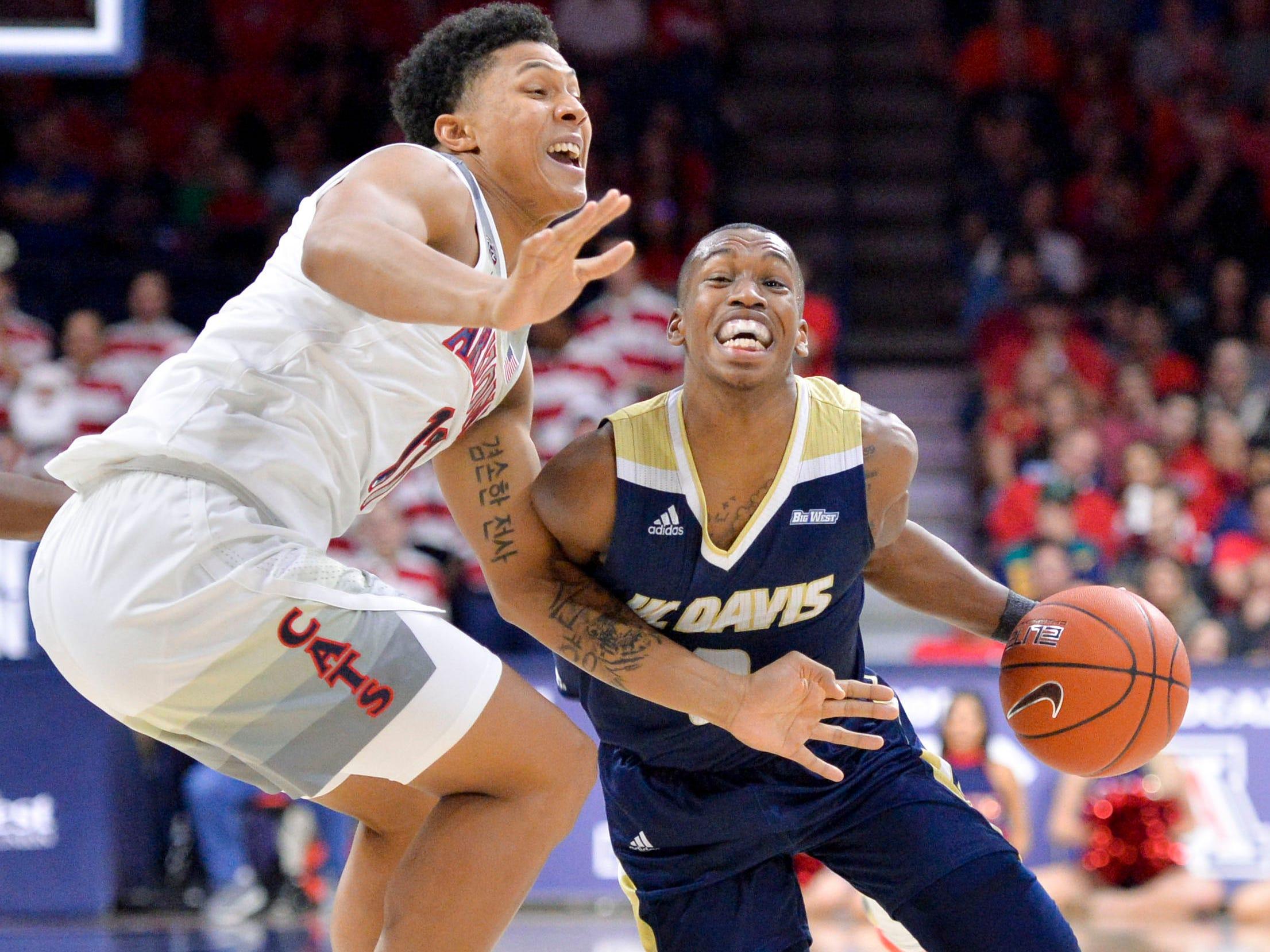 Dec 22, 2018; Tucson, AZ, USA; UC Davis Aggies guard TJ Shorts II (0) drives to the basket as Arizona Wildcats forward Ira Lee (11) defends during the first half at McKale Center. Mandatory Credit: Casey Sapio-USA TODAY Sports