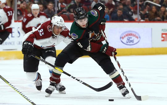 Arizona Coyotes center Nick Schmaltz (8) tries to keep the puck away from Colorado Avalanche left wing Matt Nieto (83) during the second period of an NHL hockey game Saturday, Dec. 22, 2018, in Glendale, Ariz. (AP Photo/Ross D. Franklin)