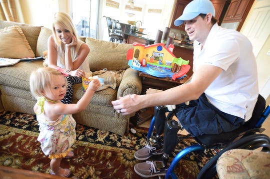 In this April 1, 2015, file photo, retired Air Force Airman Brian Kolfage, right, gives a piece of cheese to his 1-year-old daughter Paris as his wife, Ashley Kolfage, looks on at their recently rented home in Sandestin, Florida.