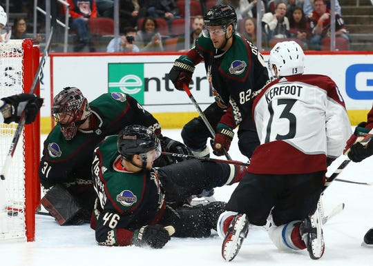 Colorado Avalanche center Alexander Kerfoot (13) gets the puck past Arizona Coyotes defenseman Ilya Lyubushkin (46), defenseman Jordan Oesterle (82) and goaltender Adin Hill (31) for a goal during the first period of an NHL hockey game Saturday, Dec. 22, 2018, in Glendale, Ariz. (AP Photo/Ross D. Franklin)