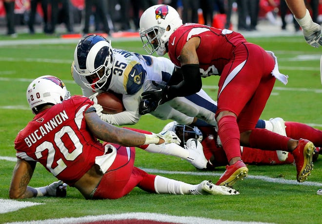 Los Angeles Rams running back C.J. Anderson (35) scores a touchdown as Arizona Cardinals outside linebacker Deone Bucannon (20) and Arizona Cardinals defensive back David Amerson defend during the first half of an NFL football game, Sunday, Dec. 23, 2018, in Glendale, Ariz.