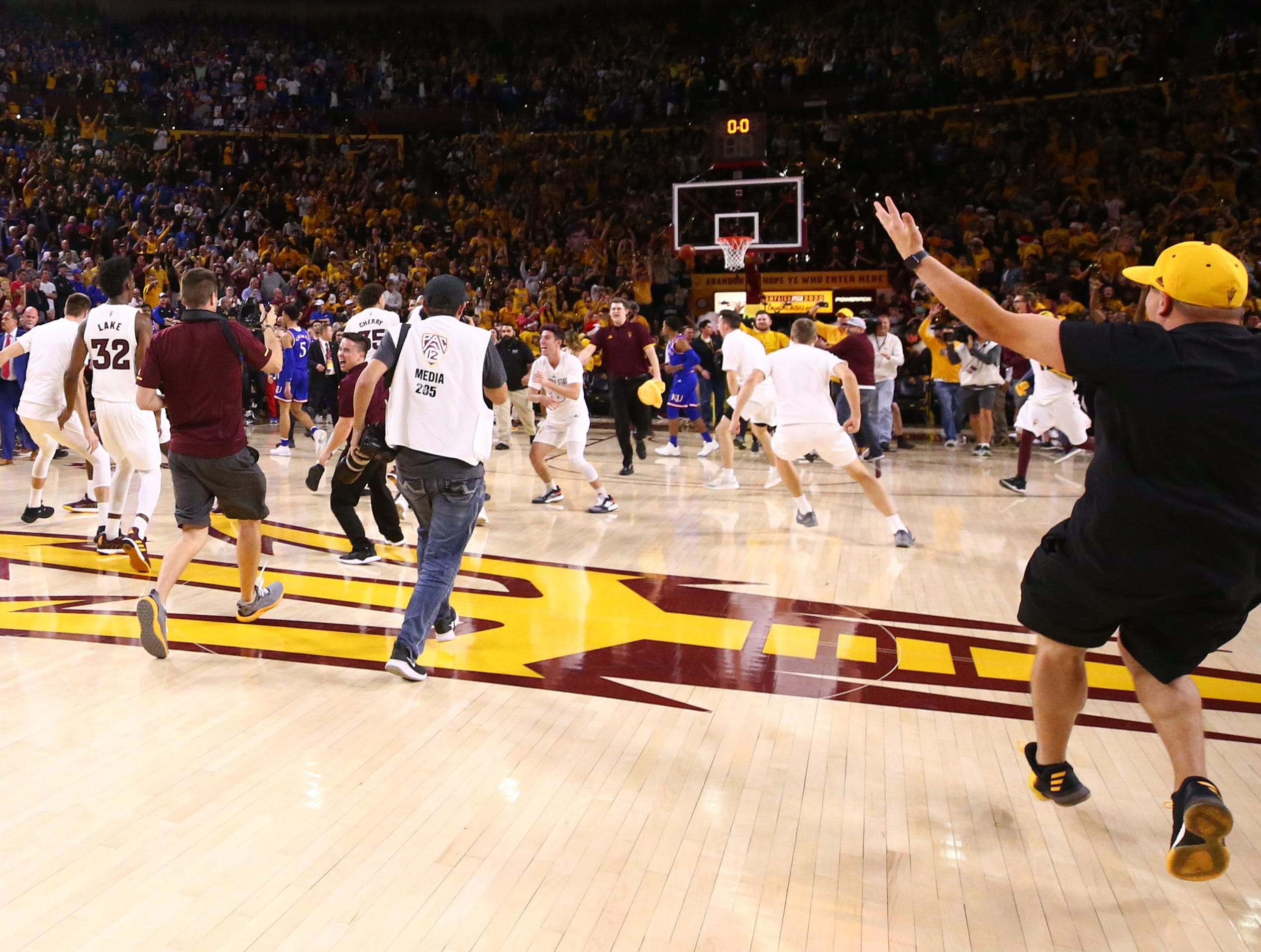 Arizona State fans rush the court after the Sun Devils defeated Kansas on Dec. 22 at Wells Fargo Arena.