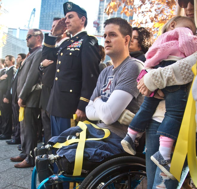 """In this Nov. 10, 2014, file photo, former U.S. Air Force Senior Airman Brian Kolfage, center, sits in a wheelchair next to his wife, Ashley, right, who holds their daughter, Paris, during the National September 11 Memorial and Museum's """"Salute to Service"""" tribute honoring U.S. veterans in New York. Kolfage, a triple amputee who lost his limbs serving in Iraq in the U.S. Air Force, started a GoFundMe page to help fund construction of President Donald Trump's border wall and raised millions of dollars."""
