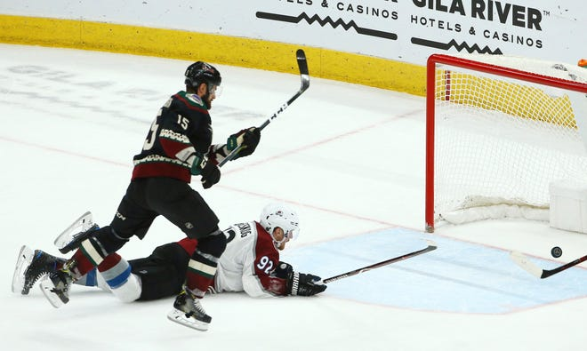 Arizona Coyotes center Brad Richardson (15) scores an empty net goal as Colorado Avalanche left wing Gabriel Landeskog (92) is unable to stop the puck during the third period of an NHL hockey game Saturday, Dec. 22, 2018, in Glendale, Ariz. The Coyotes defeated the Avalanche 6-4.