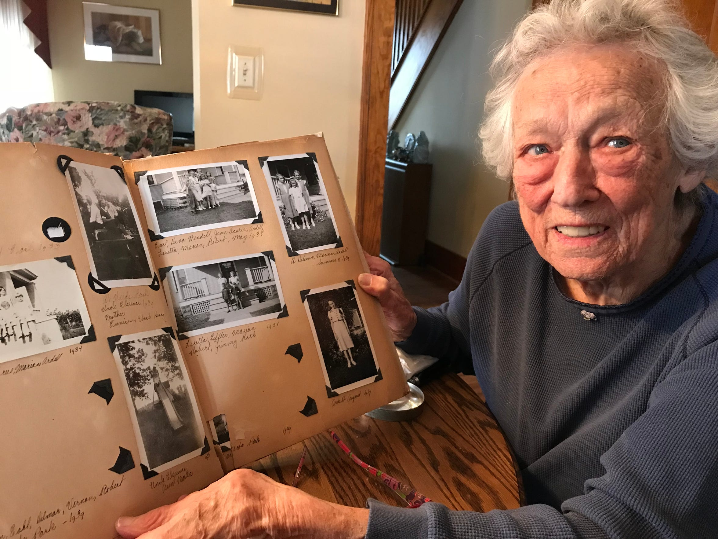 Marian Meyer with a photo album showing pictures of James Roth as a child.
