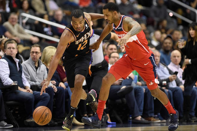 Phoenix Suns forward T.J. Warren (12) dribbles the ball against Washington Wizards forward Trevor Ariza (1) during the first half of an NBA basketball game, Saturday, Dec. 22, 2018, in Washington.