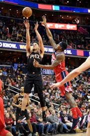 Phoenix Suns guard Devin Booker (1) shoots against Washington Wizards guard Bradley Beal (3) during the first half of an NBA basketball game, Saturday, Dec. 22, 2018, in Washington. (AP Photo/Nick Wass)