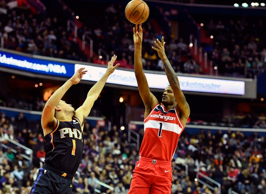 Dec 21, 2018; Washington, DC, USA; Washington Wizards forward Trevor Ariza (1) shoots over Phoenix Suns guard Devin Booker (1) during the second quarter at Capital One Arena. Mandatory Credit: Brad Mills-USA TODAY Sports