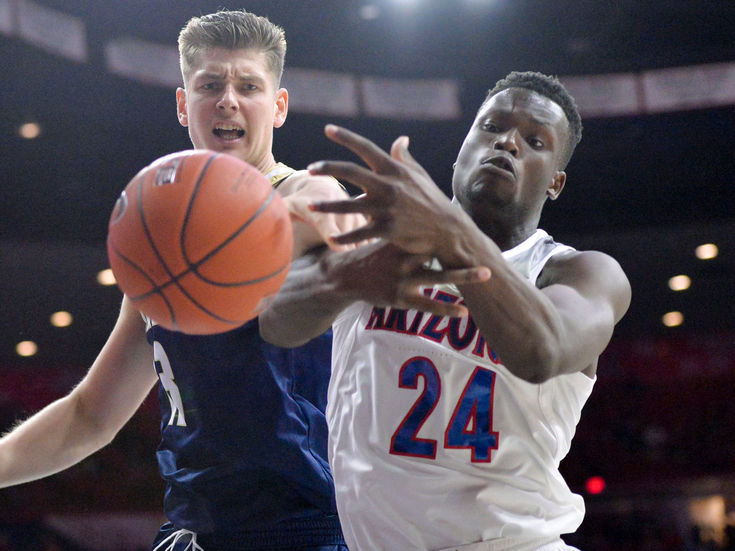Dec 22, 2018; Tucson, AZ, USA; UC Davis Aggies center Matt Neufeld (13) and Arizona Wildcats guard Emmanuel Akot (24) battle for the ball during the first half at McKale Center. Mandatory Credit: Casey Sapio-USA TODAY Sports