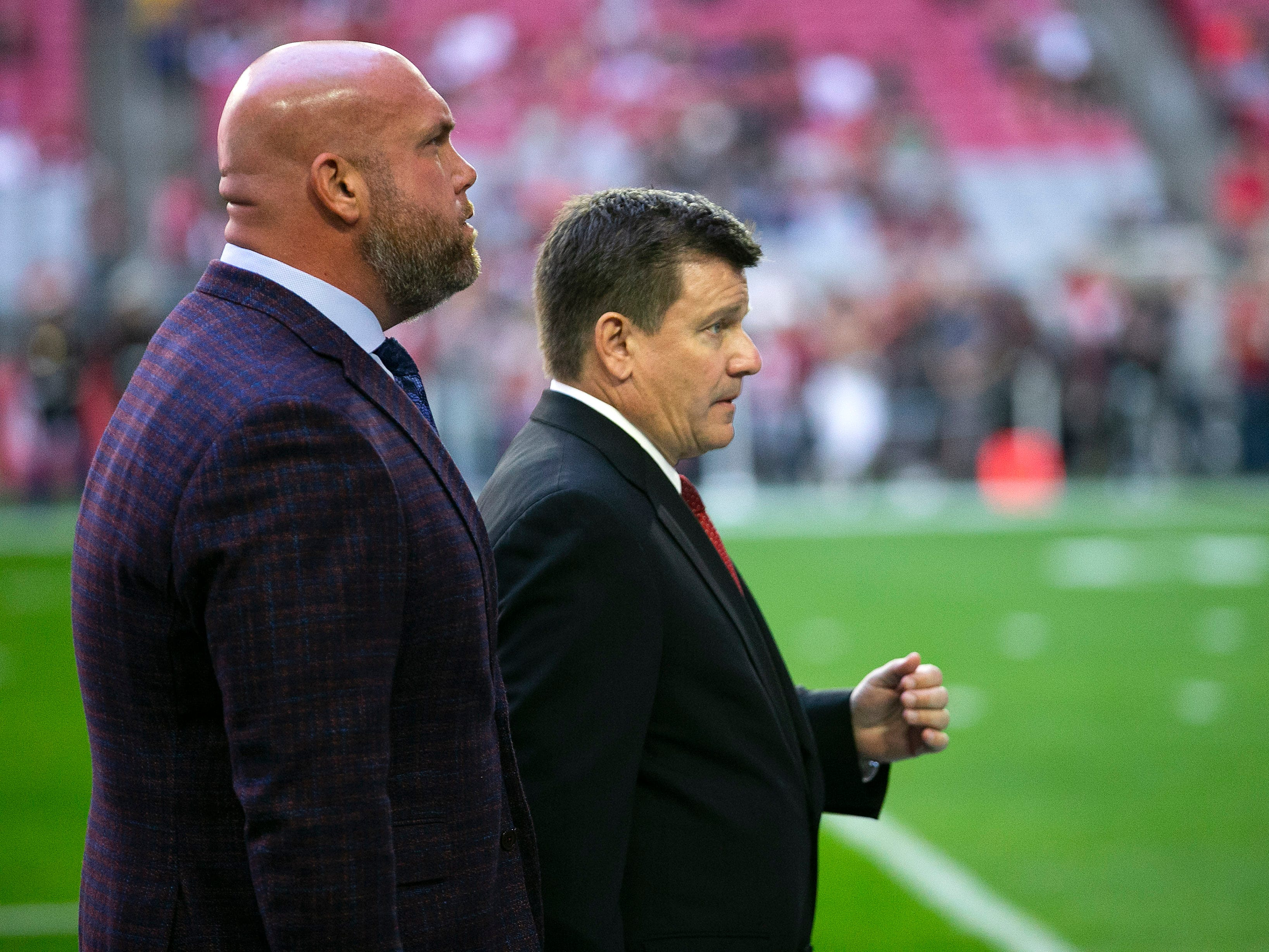 Cardinals general manager Steve Keim (left) and Cardinals president Michael Bidwill walk off the field before the pre-game routine before the start of the NFL game against the Rams at State Farm Stadium in Glendale on Sunday, December 23, 2018.