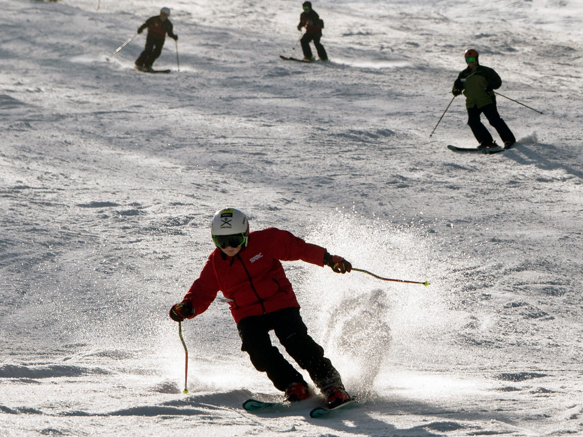 Skiers fly down Minuteman slope opening day at Roundtop Mountain Resort on Sunday.