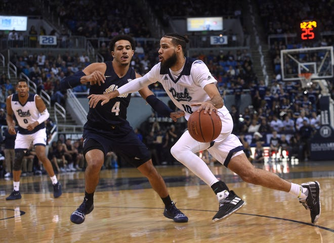 Nevada's Caleb Martin (10) drives while taking on Akron during their basketball game at Lawlor Events Center in Reno on Dec. 22, 2018.