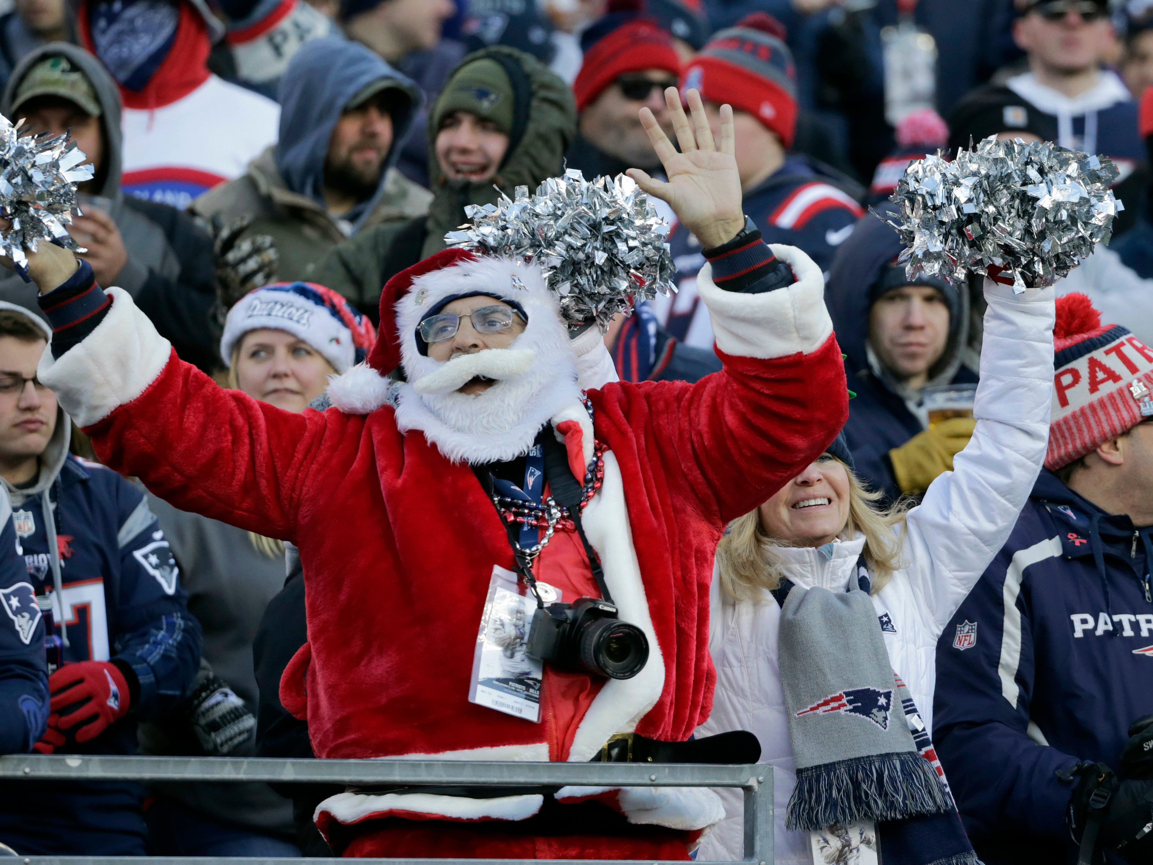Fans wearing Christmas outfits cheer during the second half of an NFL football game between the New England Patriots and the Buffalo Bills, Sunday, Dec. 23, 2018, in Foxborough, Mass. (AP Photo/Elise Amendola)