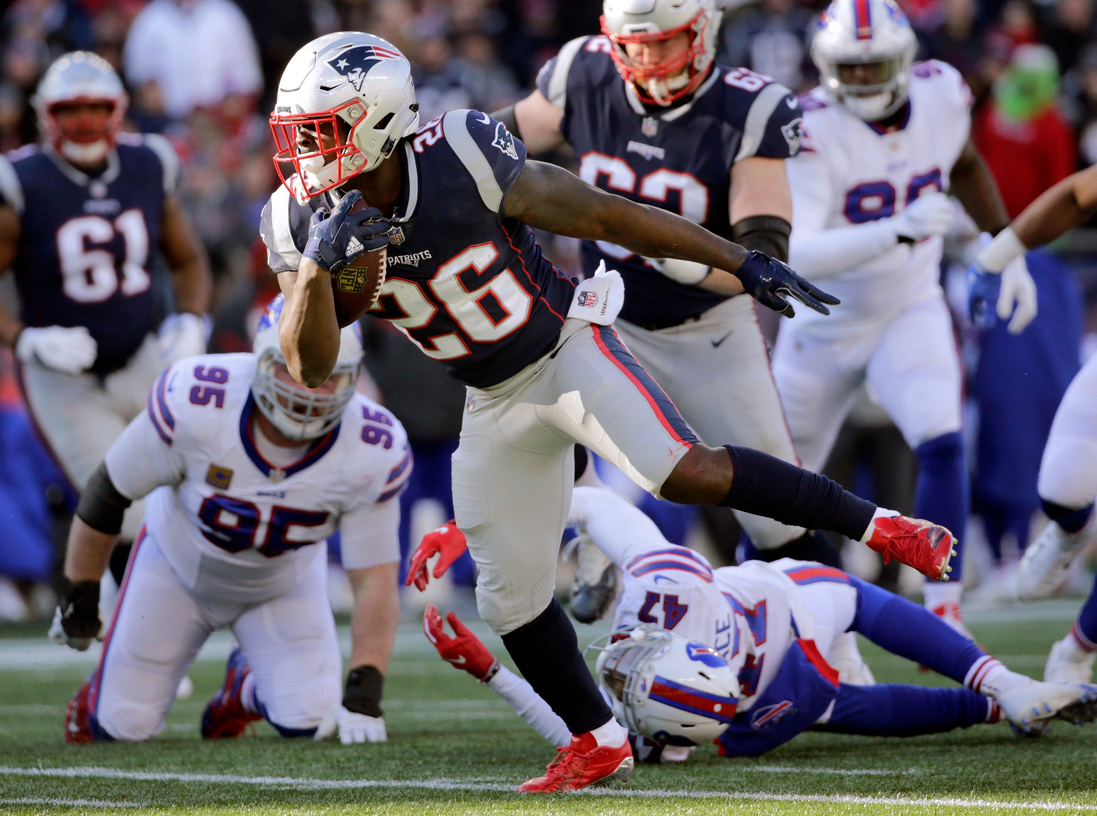 New England Patriots running back Sony Michel runs from Buffalo Bills defenders Kyle Williams (95) and Levi Wallace (47) during the first half of an NFL football game, Sunday, Dec. 23, 2018, in Foxborough, Mass. (AP Photo/Elise Amendola)