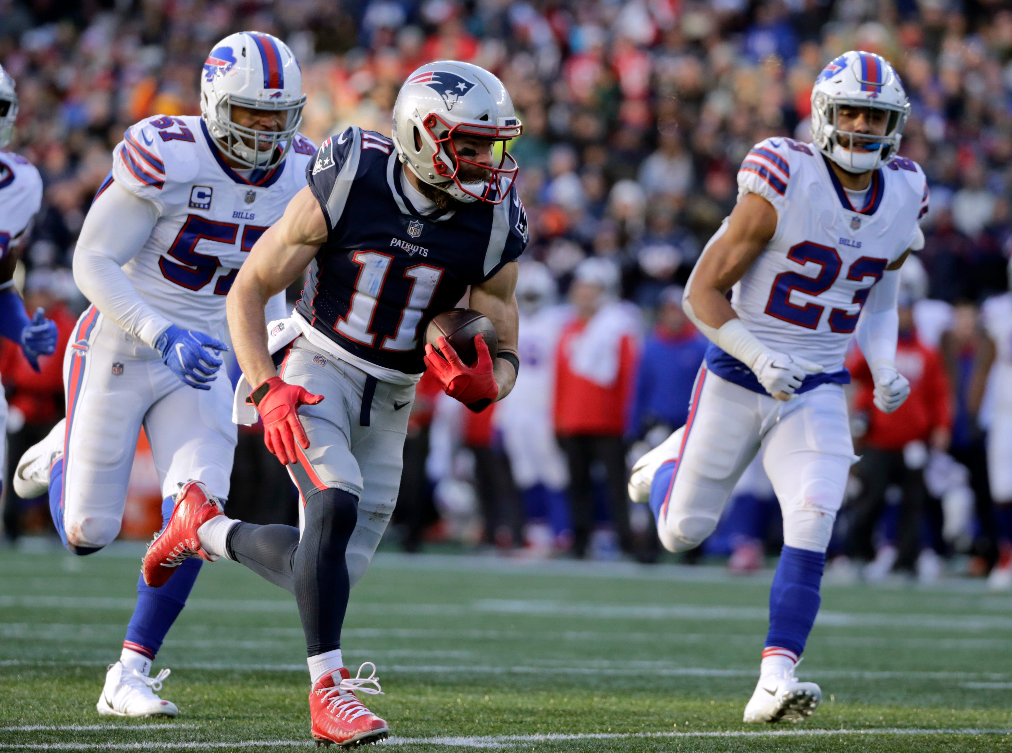 New England Patriots wide receiver Julian Edelman (11) runs from Buffalo Bills defenders Corey Thompson, left, Lorenzo Alexander and Micah Hyde, right, on his way to a touchdown after catching a pass during the second half of an NFL football game, Sunday, Dec. 23, 2018, in Foxborough, Mass. (AP Photo/Elise Amendola)