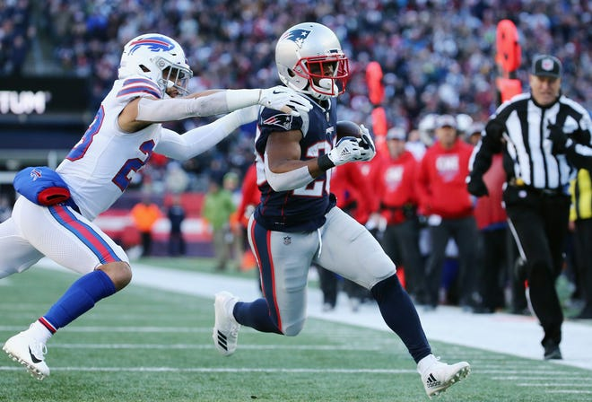 FOXBOROUGH, MA - DECEMBER 23:  James White #28 of the New England Patriots rushes for a 27-yard touchdown as Micah Hyde #23 of the Buffalo Bills is unable to make the tackle during the second quarter at Gillette Stadium on December 23, 2018 in Foxborough, Massachusetts.  (Photo by Jim Rogash/Getty Images)