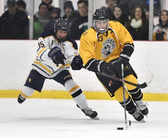 McQuaid's Jeevan Deol, right, sktaes with the puck while pressured by Victor's Lukas Miller during a regular season game played at the Rochester Ice Center, Saturday, Dec. 22, 2018. Victor beat McQuaid 2-1.