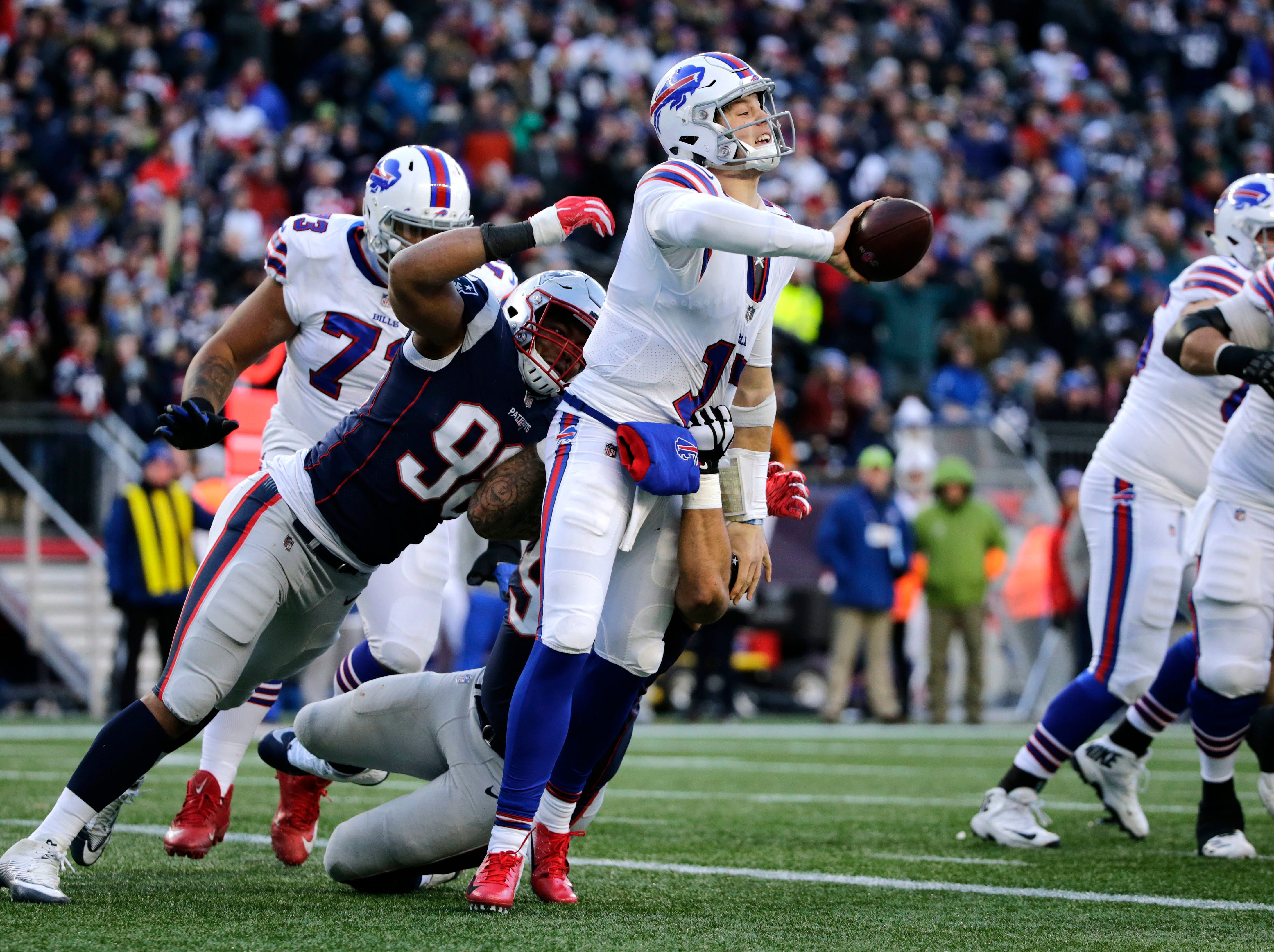 Buffalo Bills quarterback Josh Allen tries to flip the ball to a receiver as New England Patriots defenders Trey Flowers, left, and Lawrence Guy chase him down during the second half of an NFL football game, Sunday, Dec. 23, 2018, in Foxborough, Mass. (AP Photo/Elise Amendola)