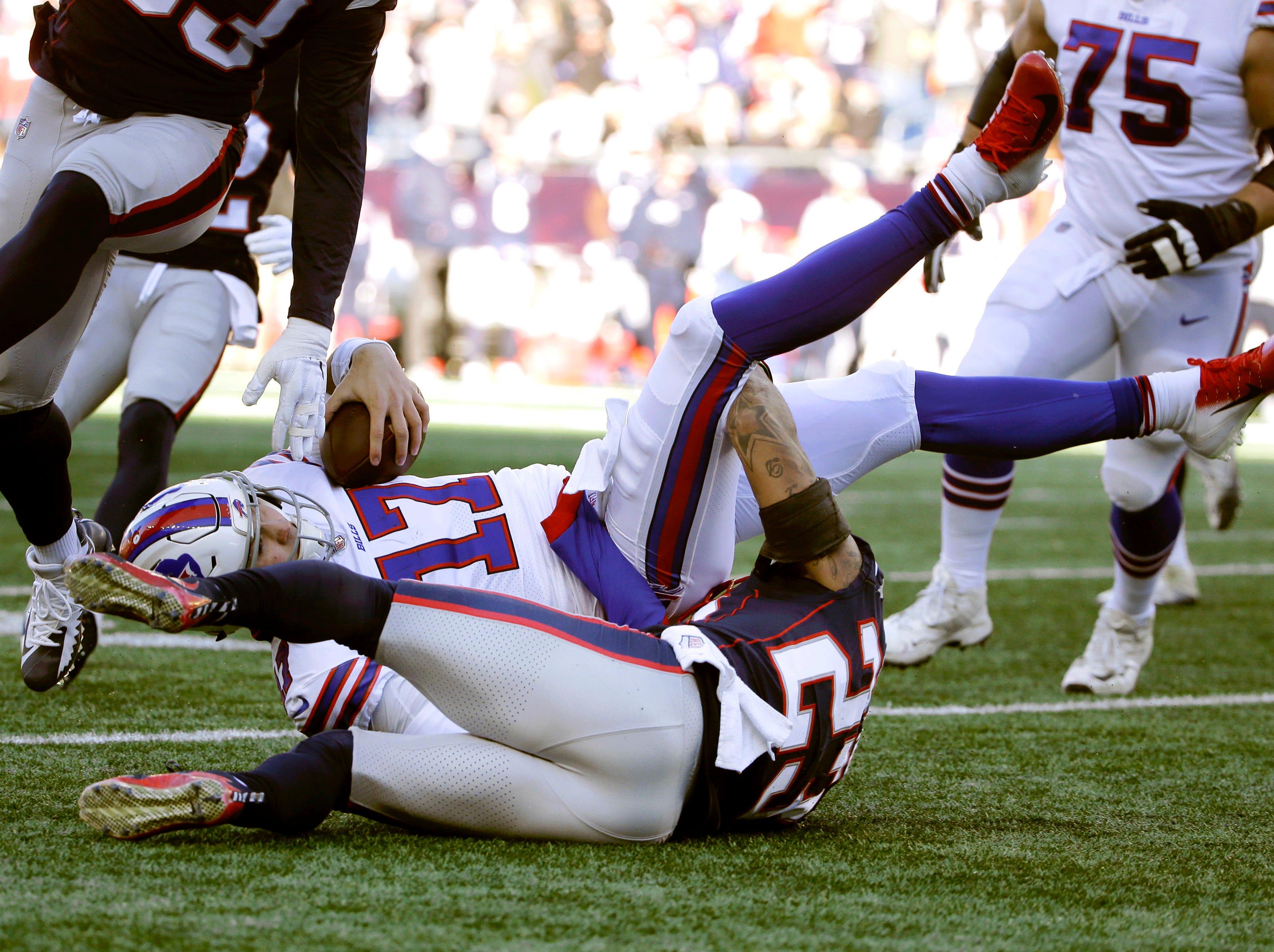 New England Patriots defensive back Patrick Chung, bottom, tackles Buffalo Bills quarterback Josh Allen during the first half of an NFL football game, Sunday, Dec. 23, 2018, in Foxborough, Mass. (AP Photo/Steven Senne)