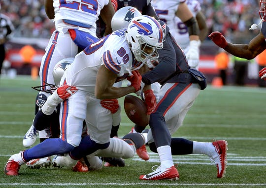 Buffalo Bills tight end Jason Croom (80) fumbles after catching a pass, as he's tackled by New England Patriots linebacker Dont'a Hightower, left rear, and defensive back Jason McCourty, right rear, during the second half of an NFL football game, Sunday, Dec. 23, 2018, in Foxborough, Mass. (AP Photo/Steven Senne)