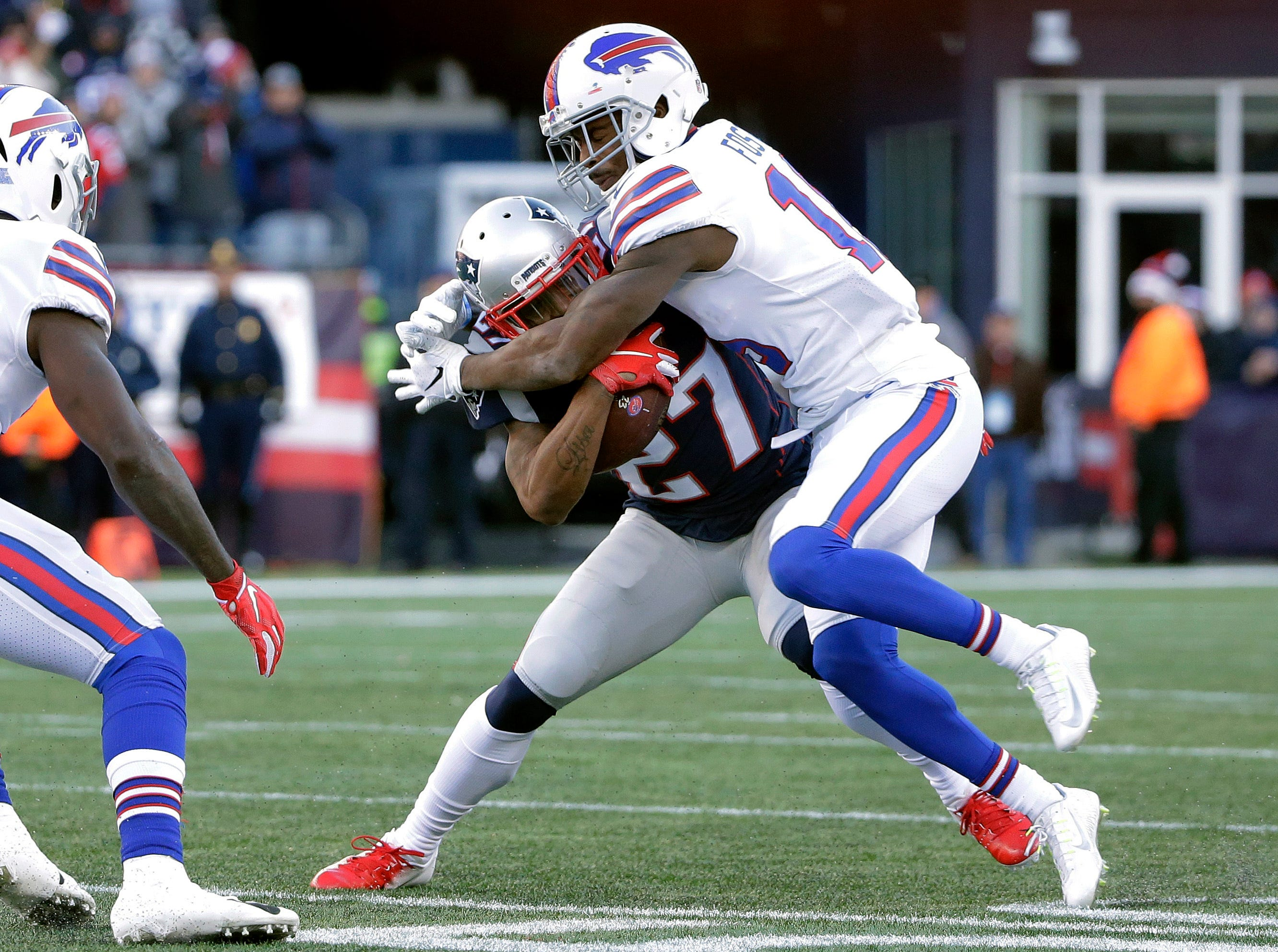 Buffalo Bills wide receiver Robert Foster, right, tackles New England Patriots defensive back J.C. Jackson (27), who intercepted a pass during the first half of an NFL football game, Sunday, Dec. 23, 2018, in Foxborough, Mass. (AP Photo/Steven Senne)