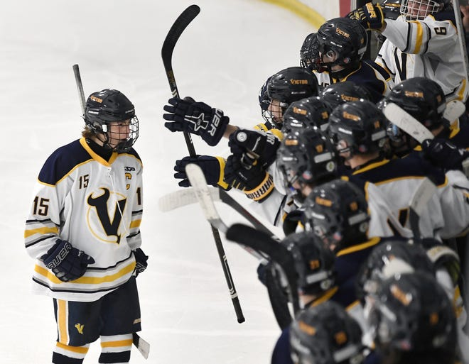 Victor's Lukas Miller, left, celebrates with teammates after his second period goal against McQuaid during a regular season game played at the Rochester Ice Center, Saturday, Dec. 22, 2018. Victor beat McQuaid 2-1.