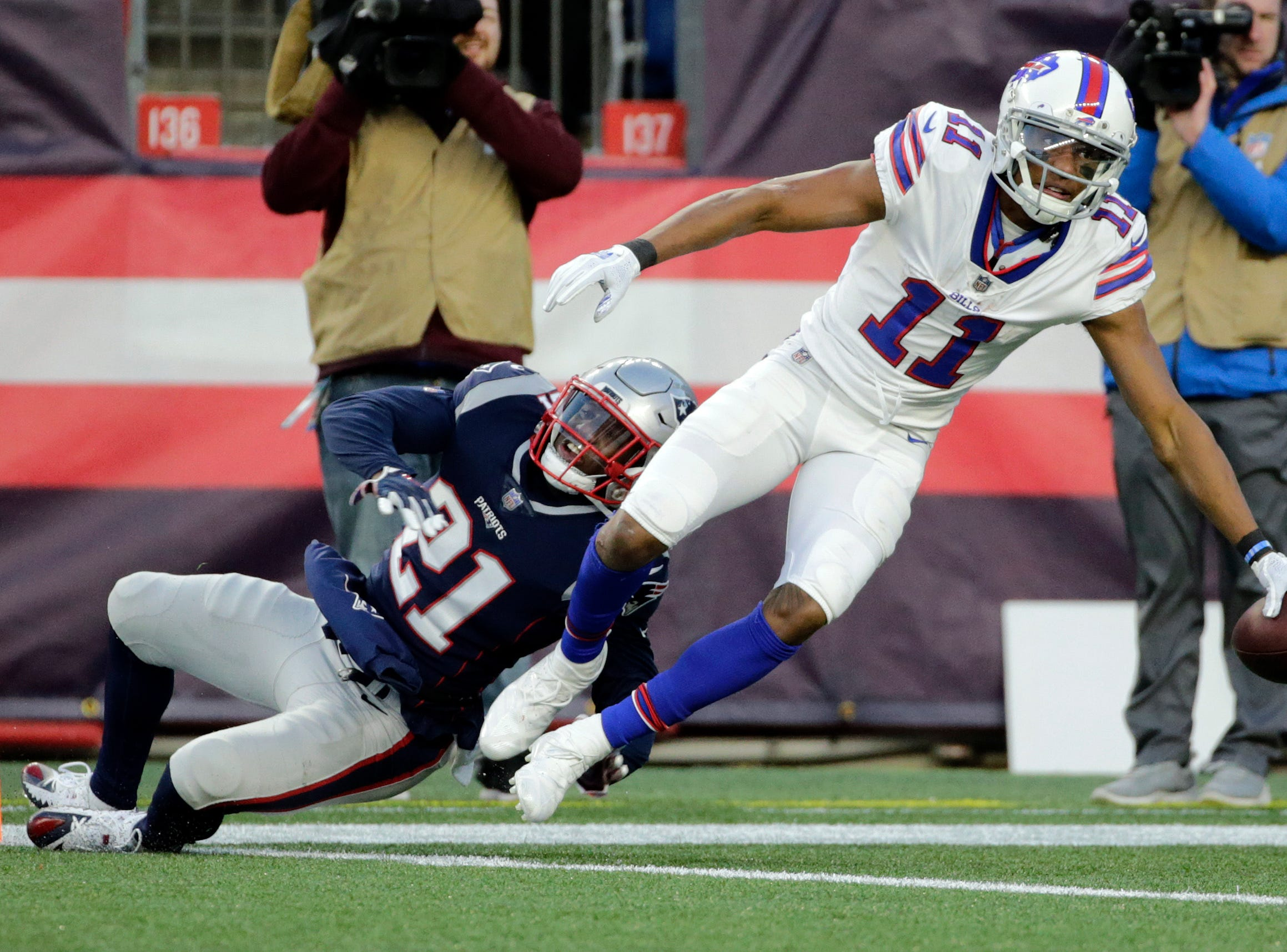 Buffalo Bills wide receiver Zay Jones (11) slips from the grasp of New England Patriots defensive back Duron Harmon (21) and reaches across the goal line for a touchdown during the second half of an NFL football game, Sunday, Dec. 23, 2018, in Foxborough, Mass. (AP Photo/Elise Amendola)