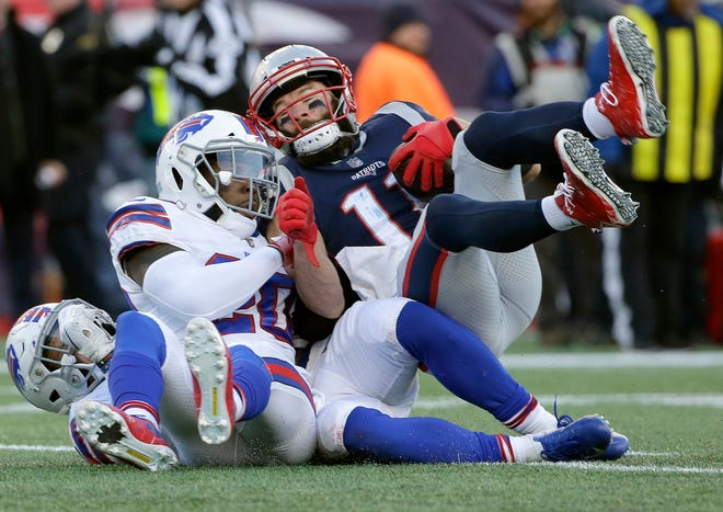 New England Patriots wide receiver Julian Edelman, right, rolls over Buffalo Bills defenders including Rafael Bush (20) on the way to a touchdown after catching a pass during the second half of an NFL football game, Sunday, Dec. 23, 2018, in Foxborough, Mass. (AP Photo/Steven Senne)