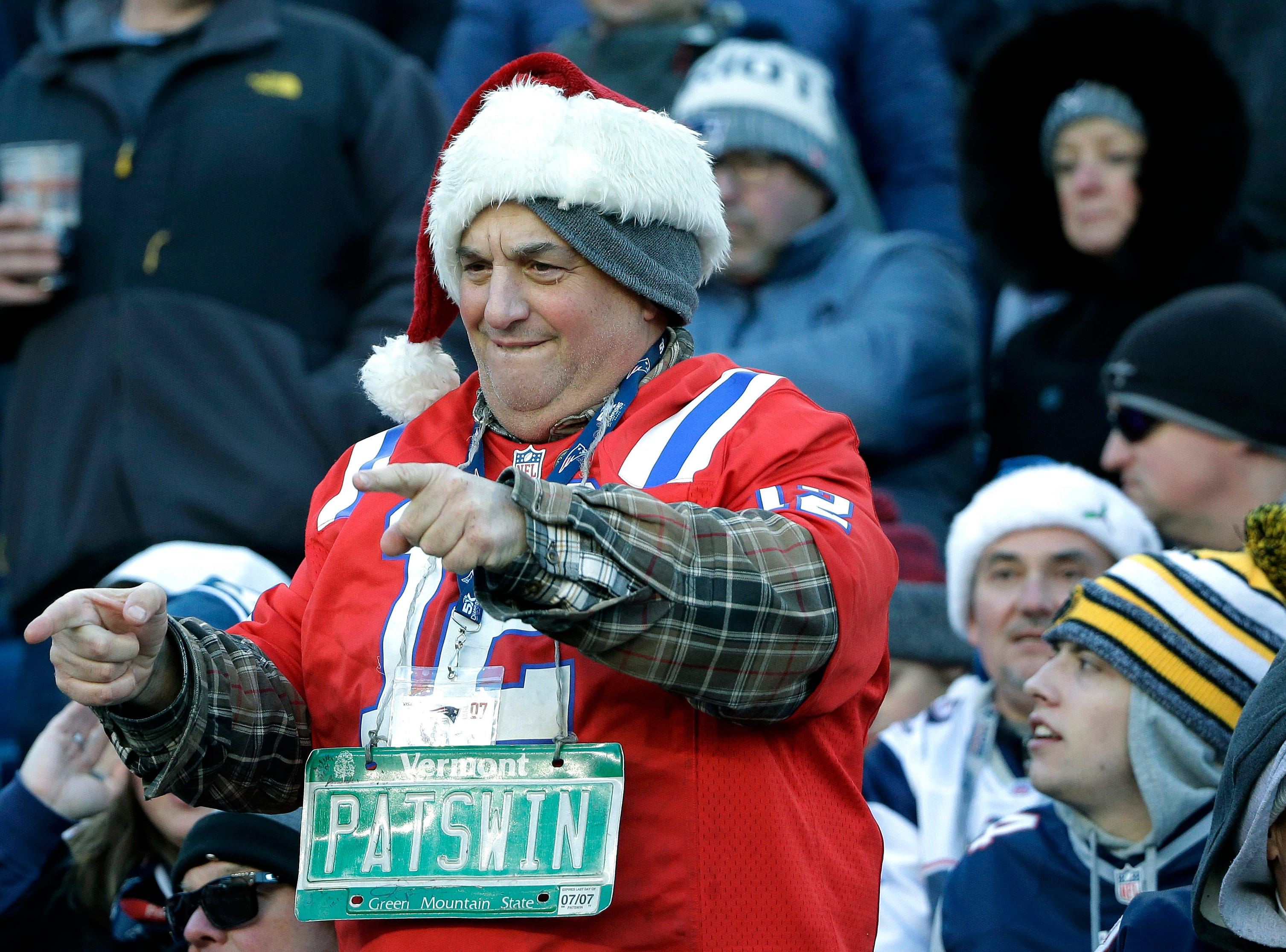 A New England Patriots fan wearing a Christmas outfit celebrates during the second half of an NFL football game between the Patriots and the Buffalo Bills, Sunday, Dec. 23, 2018, in Foxborough, Mass. (AP Photo/Steven Senne)