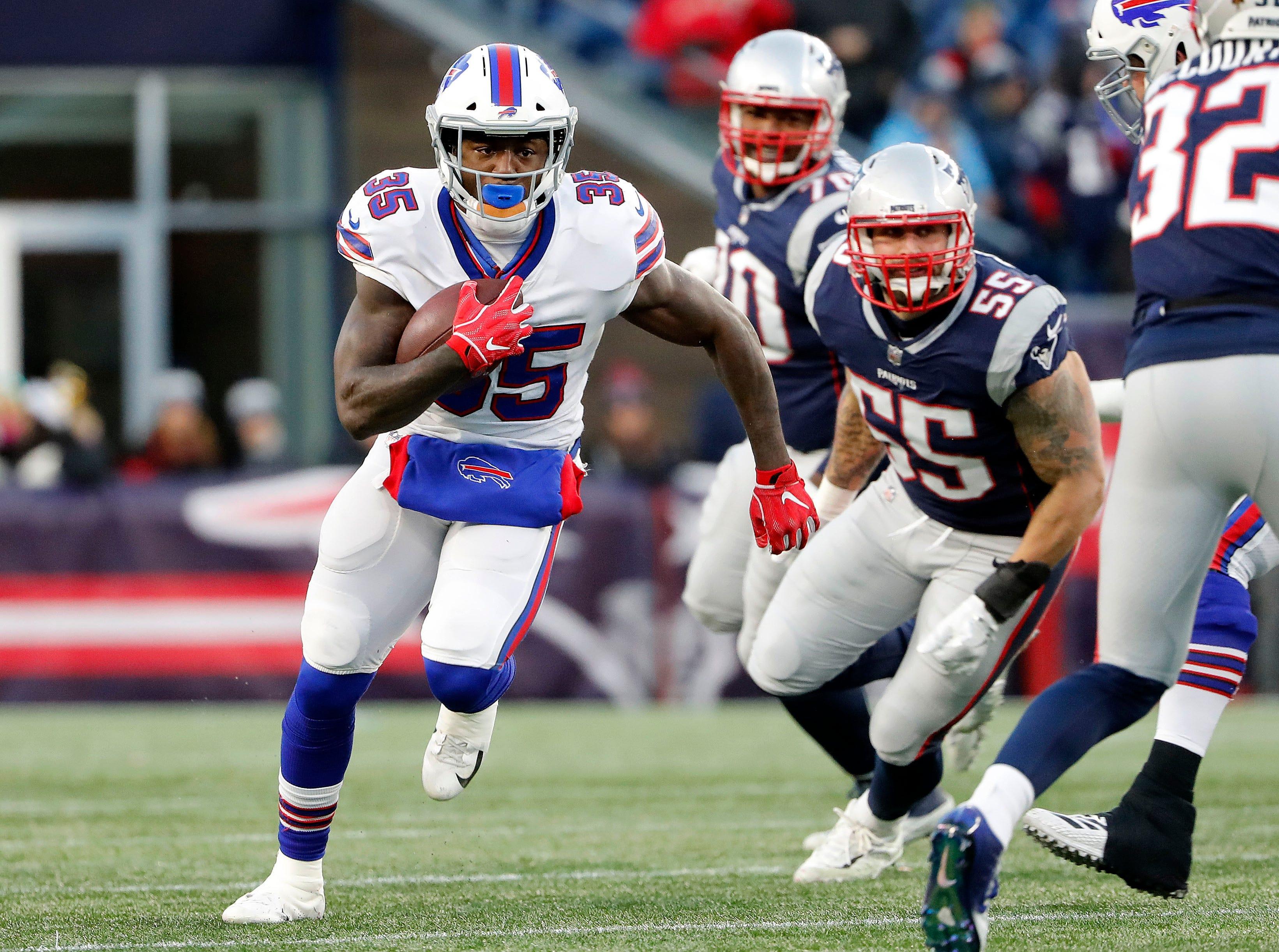 Buffalo Bills running back Keith Ford (35) runs past New England Patriots outside linebacker John Simon (55) during the second half at Gillette Stadium.
