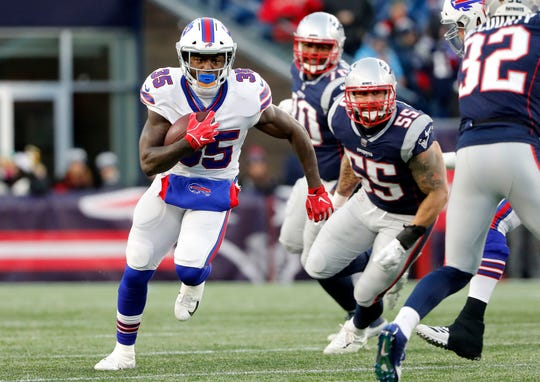 Buffalo Bills running back Keith Ford (35) runs past New England Patriots outside linebacker John Simon (55) during the second half at Gillette Stadium.