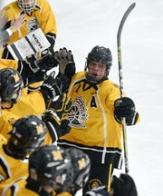 McQuaid's Charlie Merkley celebrates his goal with teammates during a regular season game against Victor played at the Rochester Ice Center, Saturday, Dec. 22, 2018.